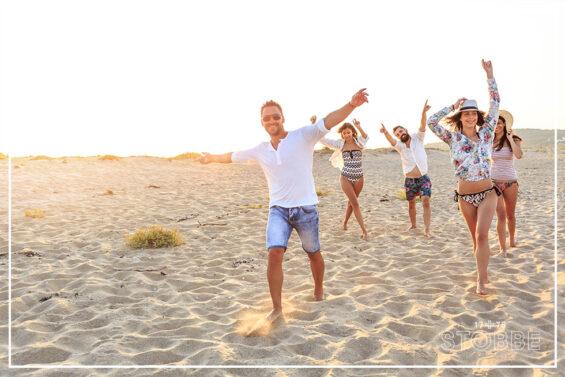 Menschen fröhlich und ausgelassen am Strand